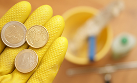 Eine Hand im gelben Handschuh hält ein paar Euromünzen. Im Hintergrund sind unscharf Putzutensilien zu erkennen.