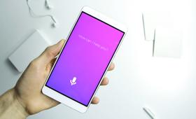 Eine Hand hält ein weißes iPhone. Der Sprachassistent Siri fragt: How can i help you? Im Hintegrund liegen auf einem weißen Tisch weiße Kopfhörer.
