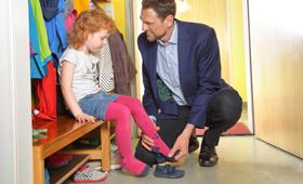 Vater holt Tochter vom Kindergarten ab und zieht ihr im Flur die Schuhe an