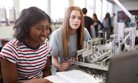 Zwei junge Frauen arbeiten in einem Klassenraum an einem Roboter