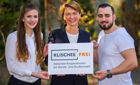 Elke Büdenbender hält ein Schild dem Logo der Klischeefrei-Initiative. Links neben ihr steht eine junge Frau, die angehende Mikrotechnologin ist. Rechts neben ihr steht ein junger Mann, der zahnmedizinischer Fachangestellter ist.