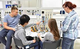 Eine Gruppe Jugendlicher beim Elektronikunterricht in der Berufsschule mit Lehrerin
