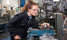 Junge Handwerkerin mit Schutzbrille an Werkbank