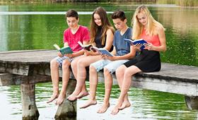 Vier Jugendliche sitzen am Rand eines Stegs an einem See und lesen jeweils ein Buch