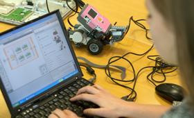 Junge Frau sitzt am Laptop und programmiert, neben ihr auf dem Tisch liegt ein kleiner Roboter