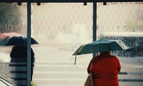 Ältere Frau mit Regenschirm an einer Bushaltestelle