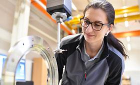Klischeefrei: Frau am Messgerät im Maschinenbau kontrolliert Bauteil auf Fertigungstoleranzen