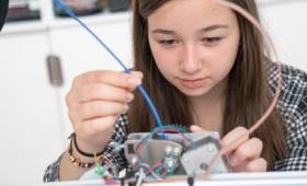 klischeefrei: Mädchen Lust auf Technik machen. Das Foto zeigt ein Mädchen, das an einer elektronischen Installation arbeitet