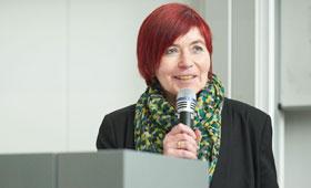 Porträt der Geschäftsführerin Lizzynet bei einer Veranstaltung, in der sie in ein Mikrophon in der Hand hält