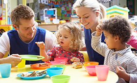Ein Erzieher und eine Erzieherin sitzen im Kindergarten zusammen mit zwei Kindern an einem Essenstisch