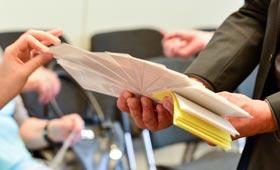 Eine Teilnehmende einer Übung wählt aus einem Fächer eine Karte aus