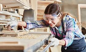 Junge Tischlerin schleift Holz mit einer Schleifmaschine