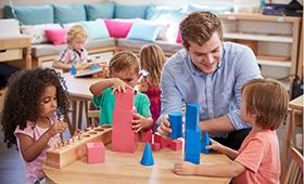 Erzieher in einer Kindertagesstätte stapelt mit Kindern Bauklötze aufeinander