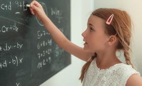 Mädchen löst Matheaufgabe an einer Tafel