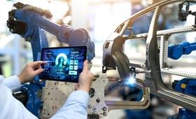 Hände einer Ingenieurin, die auf einem Tablet eine Software steuert. Im Hintergrund der Arm eines Roboters in einer Autofabrik