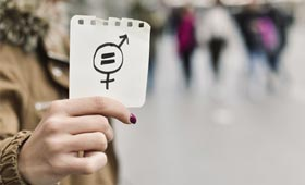 Frau hält einen Zettel mit Symbolen für Gendergerechtigkeit in der Hand