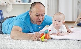 Vater liegt bäuchlings auf dem Boden und spielt mit Baby