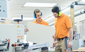 Frau und Mann besprechen etwas an einer Maschine in einer Werkstatt