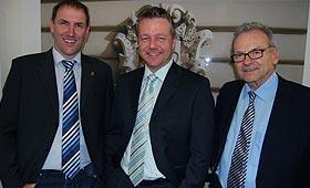 Thilo Kiess (Mitte) mit zwei Kollegen. Sie tragen Anzüge und schauen lächelnd in die Kamera.