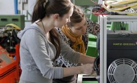 zwei Junge Frauen arbeiten an einem elektronischen Gerät