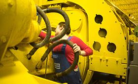 Junge Frau im Blaumann arbeitet an einer großen gelben Maschine