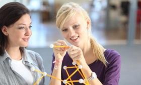 Zwei Mädchen arbeiten an einem Plastik-Modell chemischer Verbindungen