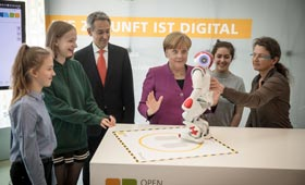 Bundeskanzlerin Merkel macht sich mit Schülerinnen vertraut mit einem Roboter.