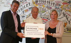 Miguel Diaz hält mit Oberbürgermeister Pit Clausen und der Gleichstellungsbeauftragten Ilse Buddemeier ein Schild mit dem Logo der Initiative hoch.