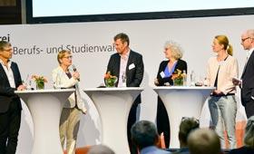 Alle Gesprächsteilnehmenden auf der Bühne: Dr. Faulstich-Wieland hat das Wort. Die anderne Teilnehmenden hören zugewandt und aufmerksam zu.