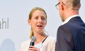Auf der Bühne: Katharina Hochfeld spricht dem Moderator zugewandt. Neben ihr Sonja Schwarz und Miguel Diaz.