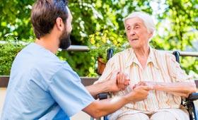 Pfleger kümmert sich liebevoll um Seniorin: Er hält ihre Hände und beide haben freundlichen Blickkontakt