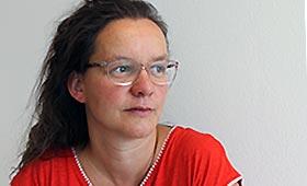 Porträtfoto einer Frau mit braunen langen Haaren und einer Brille
