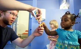 Ein junger Erzieher hilft einem Mädchen dabei, Zahnpaste auf die Zahnbürste zu tun