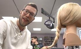 Reporter Simon frisiert einen blonden Modellkopf
