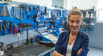 Frau steht lächelnd in ihrer Werkstatt