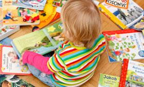 Kleinkind sitzt auf dem Boden umgeben von einer Vielzahl bunter Kinderbücher