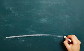 Ein Hand zeichnet einen Kreidestrich auf eine Klassenzimmertafel.
