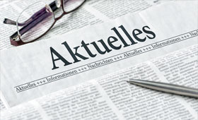 """Zeitung mit der Aufschrift """"Aktuelles"""". Auf der Zeitung liegt ein Kugelschreiber und eine Brille."""