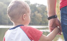 Ein kleiner Junge an der Hand seines Vaters.