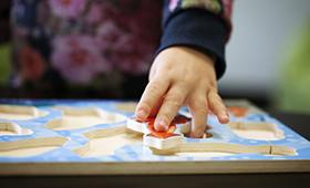 Die Hand eines Kindes an einem Steckpuzzle.