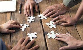 Sechs Hände auf einem Holztisch die jeweils ein Puzzleteil in die Mitte schieben.